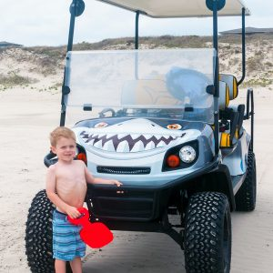 Small child posing in front of Grey Shark cart